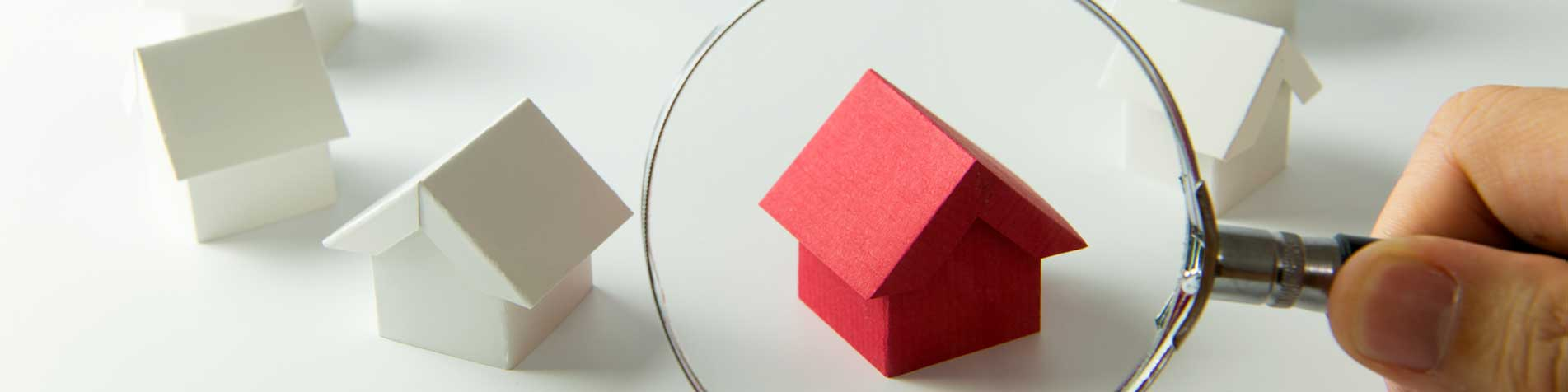 magnifying glass over red wooden house